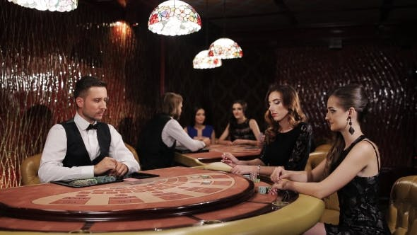 Cover Image for Two Beautiful Women Playing At The Table Blackjack In a Casino