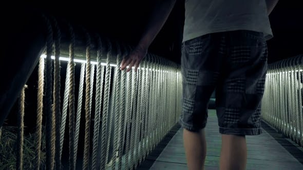 Thumbnail for Men Walking Over The Lighted Wooden Bridge
