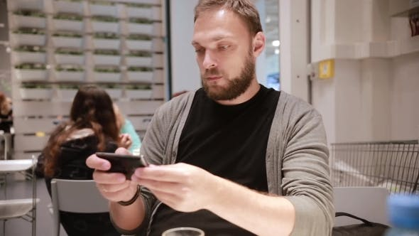 Thumbnail for Modern Technology In a Public Place. Handsome Young Man With a Beard Using His Smartphone