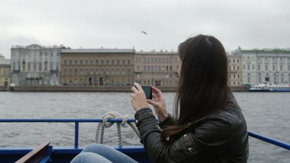 Thumbnail for Girl Sitting In a River Bus On The Go Taking Photos Of Architecture On a River Quay. A Seagull Is