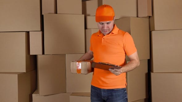 Thumbnail for Man In Orange Uniform Delivering Heavily Damaged Parcel To Customer. Brown Cartons Background