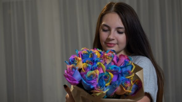 Thumbnail for Young Woman Is Smelling Bouquet Of Rainbow Roses
