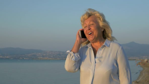 Thumbnail for On The Sea Coast City Of Perea, Greece Is Walking Woman And Talking On Mobile Phone
