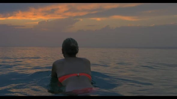 Thumbnail for Young Woman Swims Away In The Sea At Sunset, Magical View Of Evening Cloudy Sky And Calm Sea