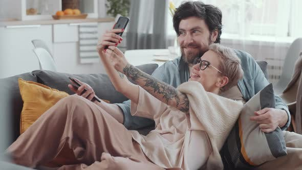Thumbnail for Happy Young Couple Taking Selfie with Smartphone on Sofa
