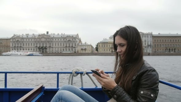 Thumbnail for Beautiful Brunette Woman Uses Her Smartphone Sitting In a River Bus, Resting. She Gladly Smiles. St