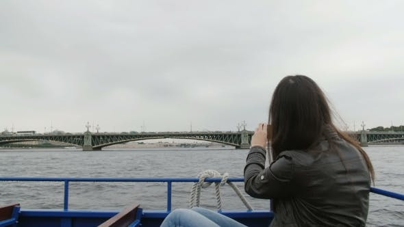Thumbnail for Young Brunette Woman Sightseeing In a River Bus. Taking Photos On a Smartphone Of a Bridge