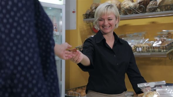 Thumbnail for Female Seller Gets Credit Card From The Client At The Pastry Shop