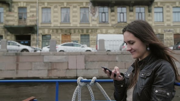 Thumbnail for Happy Brunette Girl Using Smartphone, Smiling. Beautiful Woman On a Boat Tour, Admiring Architecture