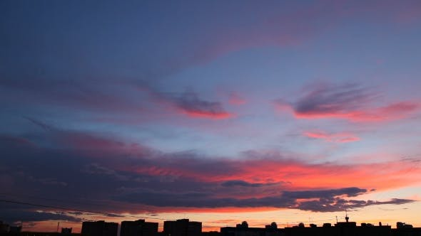 Clip Of Fluffy Clouds Over Sunset Sky. Evening Cityscape, Silhouette Of Buildings. Beautiful