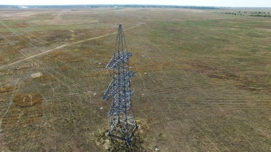 AERIAL: Flying Up The High Voltage Electricity Tower And Power Lines. Aerial Drone Shot.  30Fps