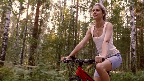 Thumbnail for Blond Girl Riding Her Bicycle In The Forest