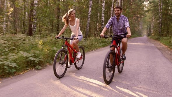 Thumbnail for Young Woman And Handsome Man Cycling Happily Together