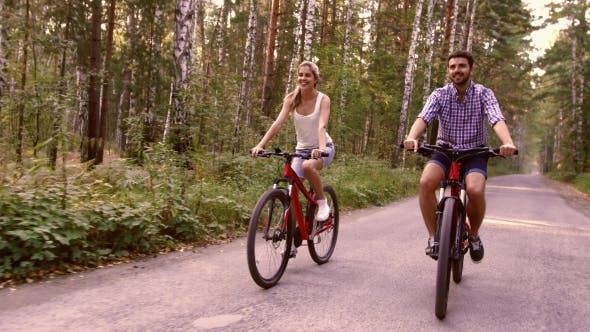 Thumbnail for Portrait Of Happy Couple Having Fun On Bicycle Ride In The Summer Park