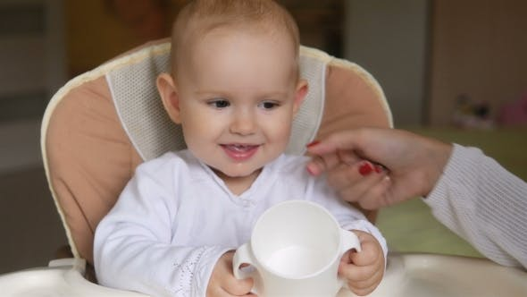 Thumbnail for Little Girl Drink Water In Child Seat And Smiling. Happy Family Concept. Mother With Spoon And Baby