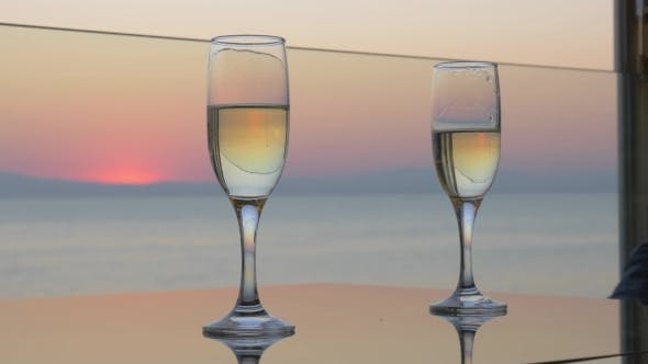 Thumbnail for Woman And Man Hands Are Clinking Glasses Of Champagne On Sunset Sea Background