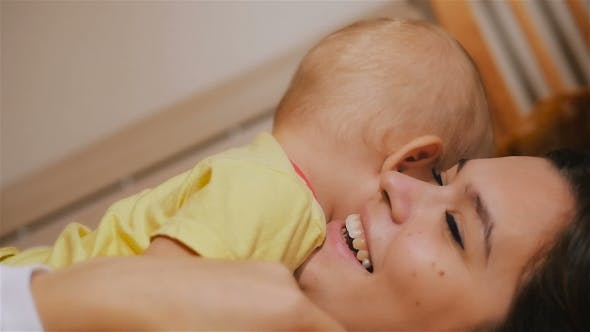 Thumbnail for Young Happy Mother Holding Her Newborn Child And Throws Up. Family At Home. Beautiful Smiling Mom