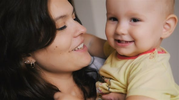 Thumbnail for Young Happy Mother Holding Her Newborn Child. Family At Home. Beautiful Smiling Mom And Happy Baby