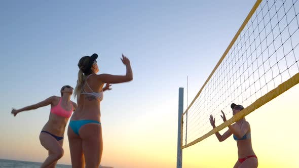Thumbnail for Women players play beach volleyball at sunset and a player hand sets the ball.