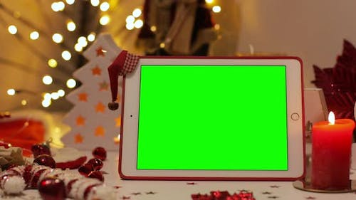iPad Air with green screen on a background of Christmas tree and holiday lights. Santa Claus hat