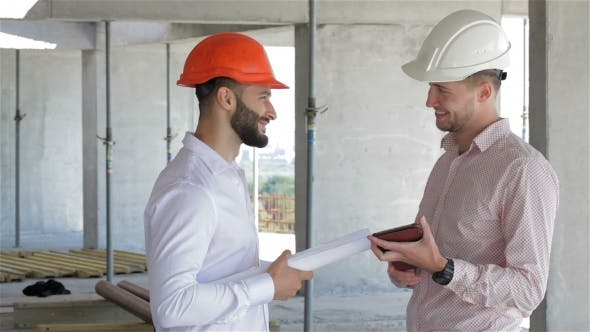 Thumbnail for Two Builders Looking At The Digital Tablet At The Building Under Construction