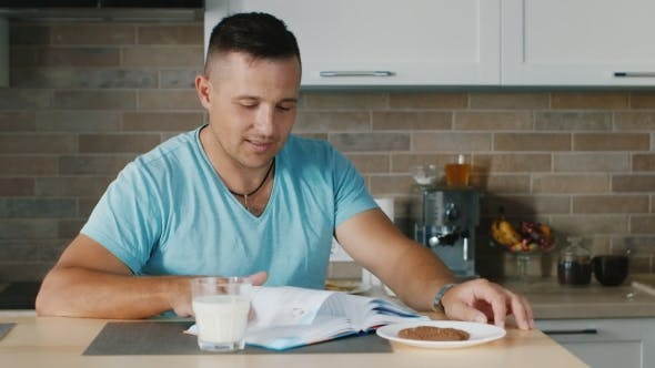 Thumbnail for Young Man Reading a Book in the Kitchen