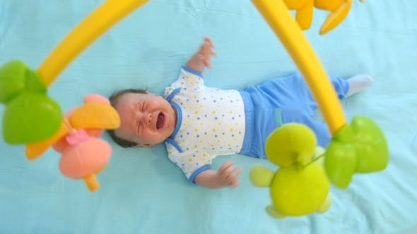 Thumbnail for Little Cute Baby Boy Lying In Crib With Toy