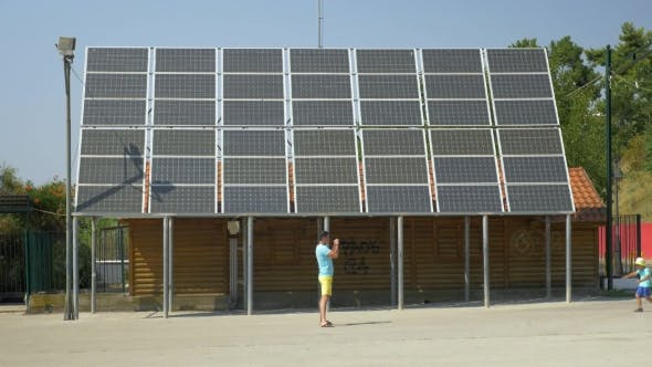 Thumbnail for Father Take Picture Of Running Son Along House With Solar Panels On Rooftop Piraeus, Greece
