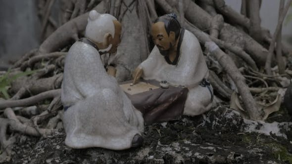 Kleine Porzellanfigur am Bonsai Baum