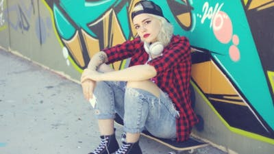 Trendy Young Urban Woman Waiting On Her Skateboard