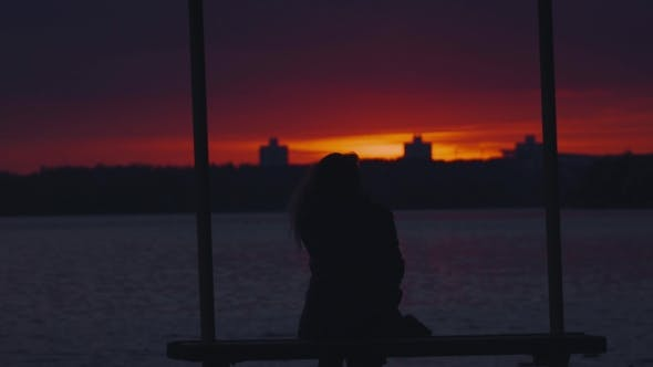 Thumbnail for Silhouette Of a Girl Sitting On a Bench And Admire The Sunset.