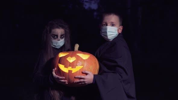 Dressed Up Children Holding Pumpkin Lantern