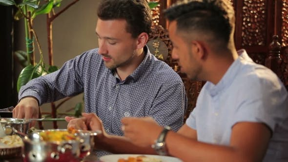 Thumbnail for Two Men Eating a Pitta In The Indian Restaurant