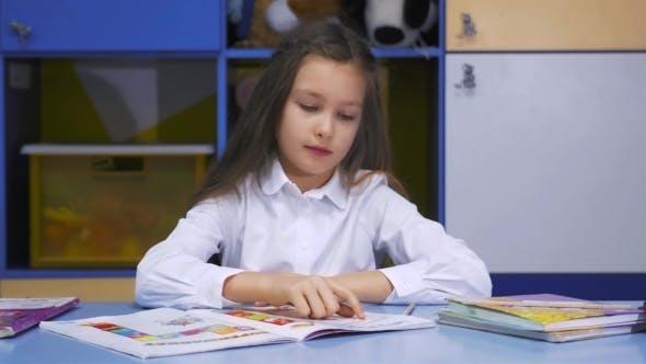 Thumbnail for Cute Little Girl Studying At The Library Doing Homework And Smiling