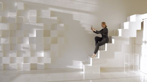 Thumbnail for In Light Studio Young Girl Sitting On Stairs And Talking By Video Call On Tablet