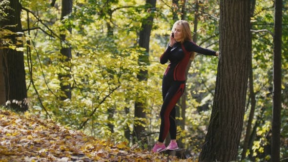 Thumbnail for Young, Sporty Woman Talking On Cellphone At Autumn Park Outdoor