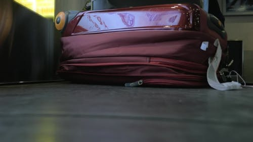 Suitcase On Luggage Conveyor Belt At Airport