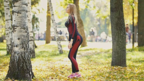 Thumbnail for Sexy Attractive Female Blonde Bikini-fitness Model Stretching In The Autumn Park On Ground Covered