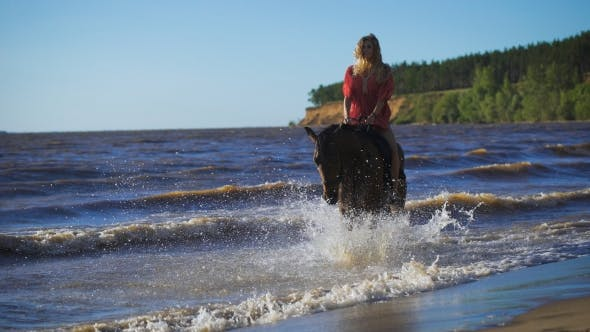 Thumbnail for A Beautiful Blonde Young Woman Riding a Horse At a Lake
