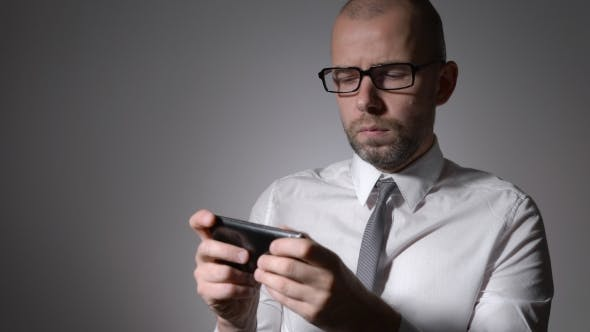 Cover Image for Businessman Or a Middle-aged Manager In Glasses Holding a Smartphone