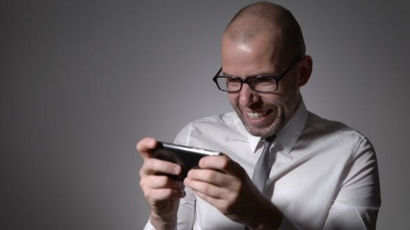 Very Expressive And Emotional Manager In White Shirt And Tie Playing Games On His Smartphone.