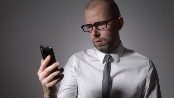 Thumbnail for A Businessman Or a Middle-aged Manager In Glasses Holding a Smartphone In The Hands