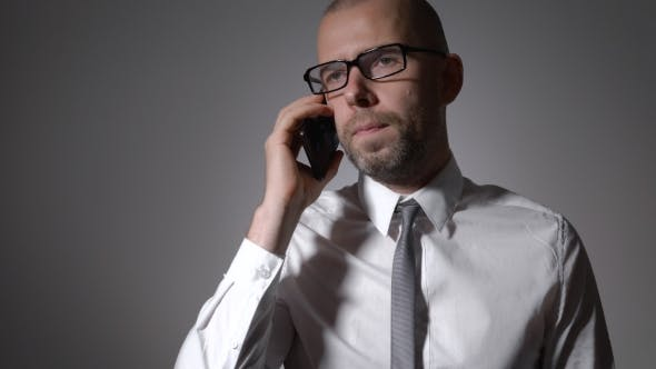 Cover Image for Businessman Leads a Serious Conversation With a Colleague On The Phone.