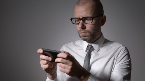 Thumbnail for A Businessman Or a Middle-aged Manager In Glasses Holding a Smartphone In The Hands And Prints In