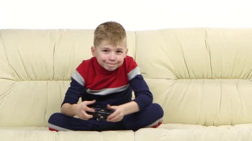 Boy with Games Console Playing Video Game on the Sofa