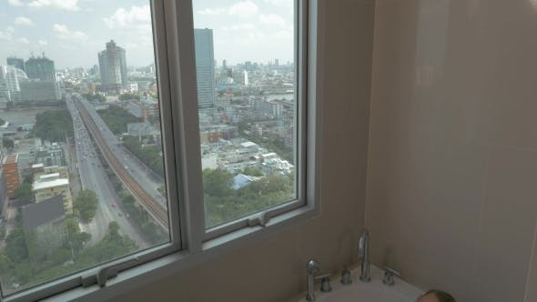 Thumbnail for In The City Of Bangkok, Thailand Young Girl In Apartment By Window Taking a Bath