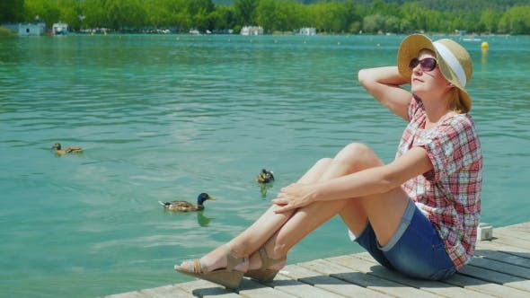 Thumbnail for A Woman Tourist Enjoying Vacation At The Lake Where Ducks Swim. Resort In Spain