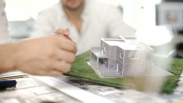 Thumbnail for Male Hand Pointing At Main Door House Miniature With a Pencil In His Office Desktop. .