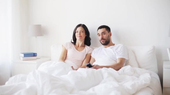 Thumbnail for Happy Couple Watching Tv In Bed At Home