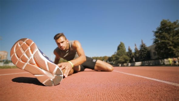Thumbnail for Male Athlet Stretches His Leg At The Stadium